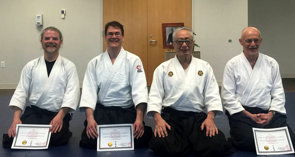 Aikido practitioners kneeling with certificates